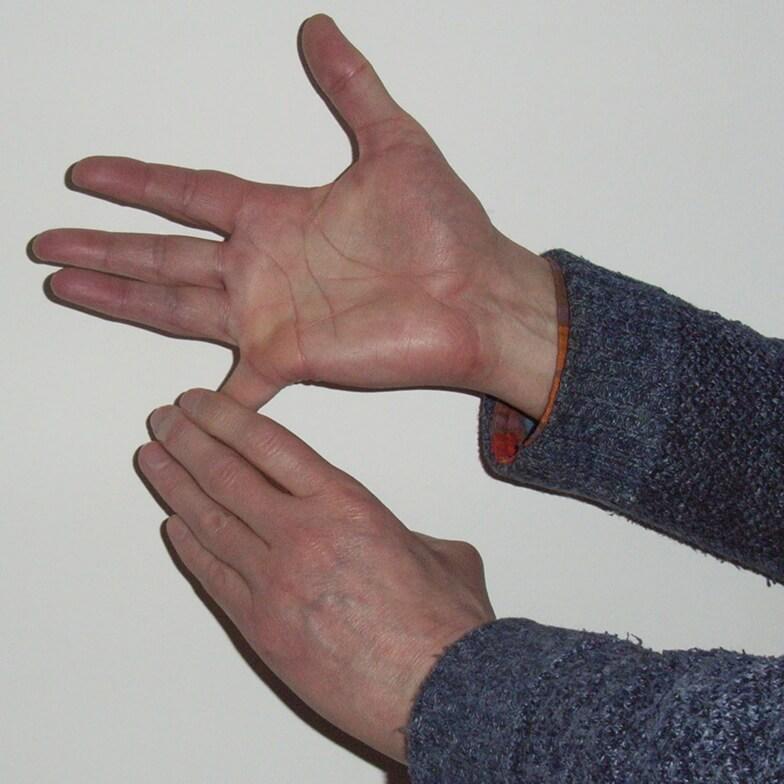 Left fingers pressing down little finger of right hand